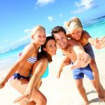AdobeStock_51696788_Licensed-Family of four having fun at the beach 1